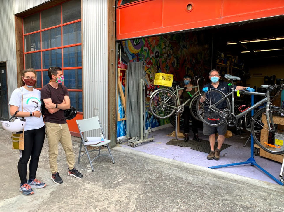 A man and woman stand wearing masks as they wait for their bikes to be repaired by two bike mechanics